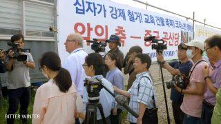 左依爾先生站在示威者和記者中間