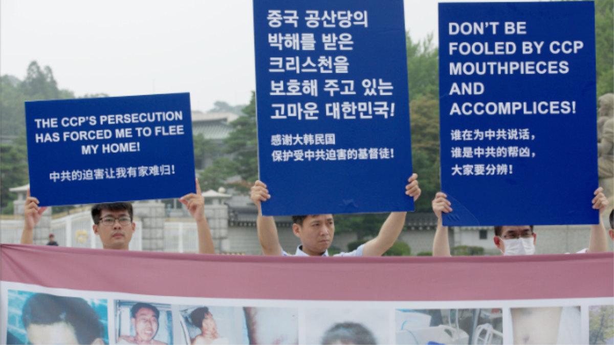 全能神教會成員舉牌控訴中共的惡行,其中一個牌子寫著:中共的迫害讓我有家難歸!(全能神教會)