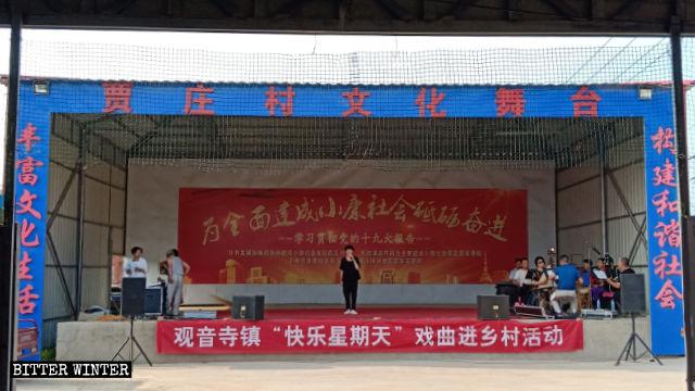 賈莊村文化戲台正在演出,戲台上掛著「快樂星期天」的橫幅